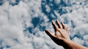a hand pointing towards the sky