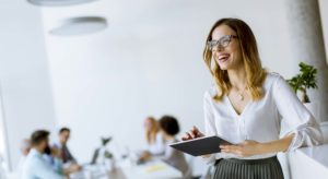 smiling woman holding a tablet in a meeting