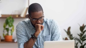 man sitting at desk in front of laptop looking confused