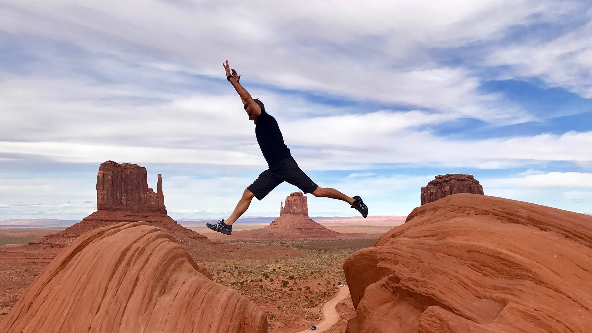 person jumping from one rock to the other with the monument valley in background