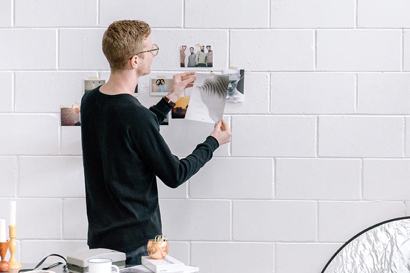 young professional hanging pictures on a wall