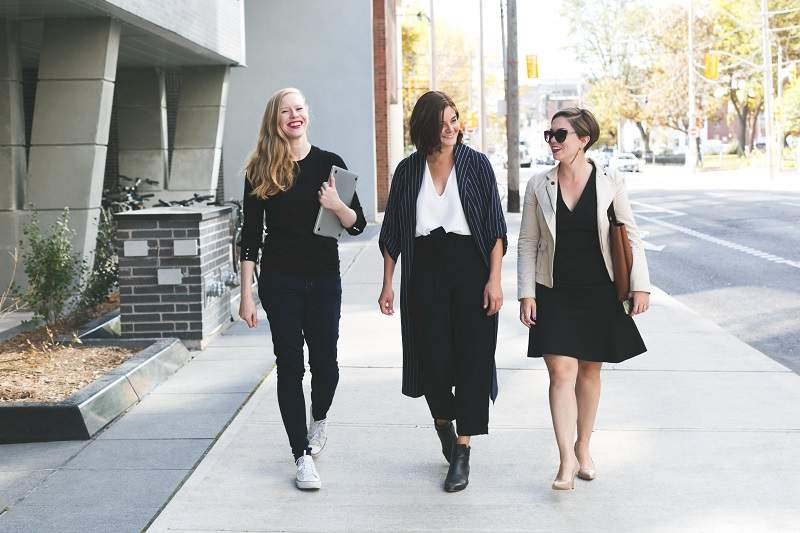 three women walking down the street