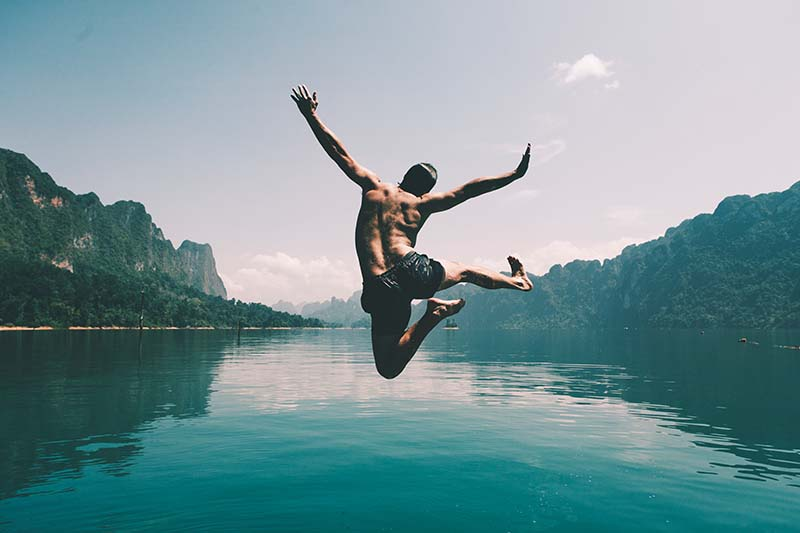 a guy jumping in a lake