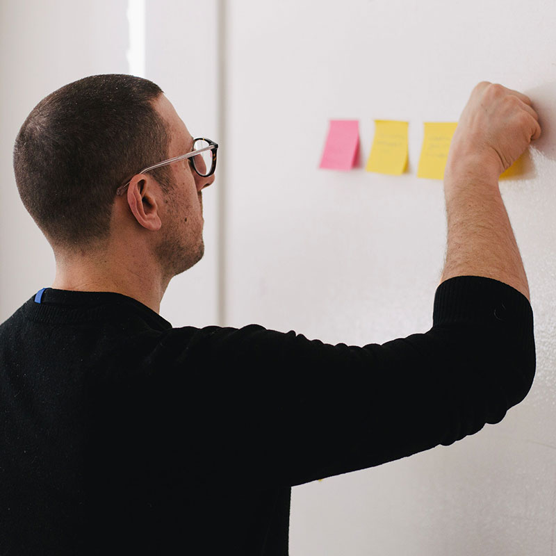 man posting sticky notes on a wall for a change management processes meeting