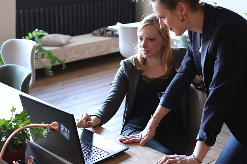 one employee showing another employee something on a laptop
