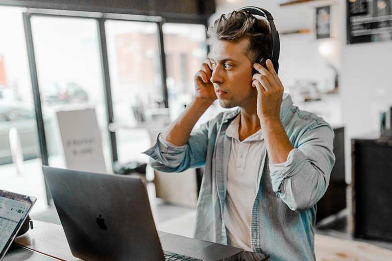 man using headphones and laptop