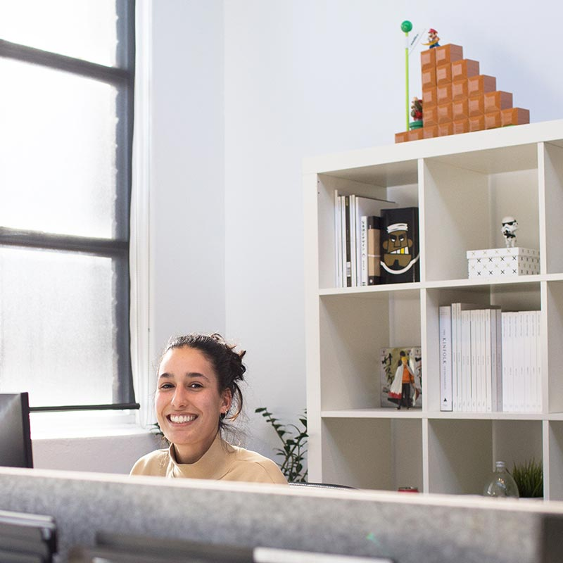 an employee at her desk smiling