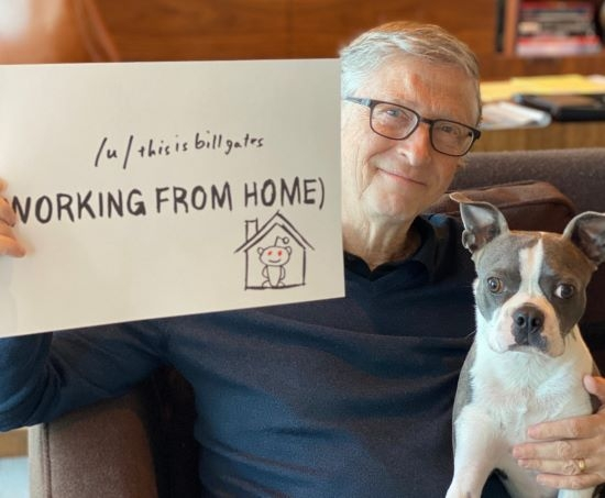 bill gates with his dog holding up a sign saying this is bill gates working from home