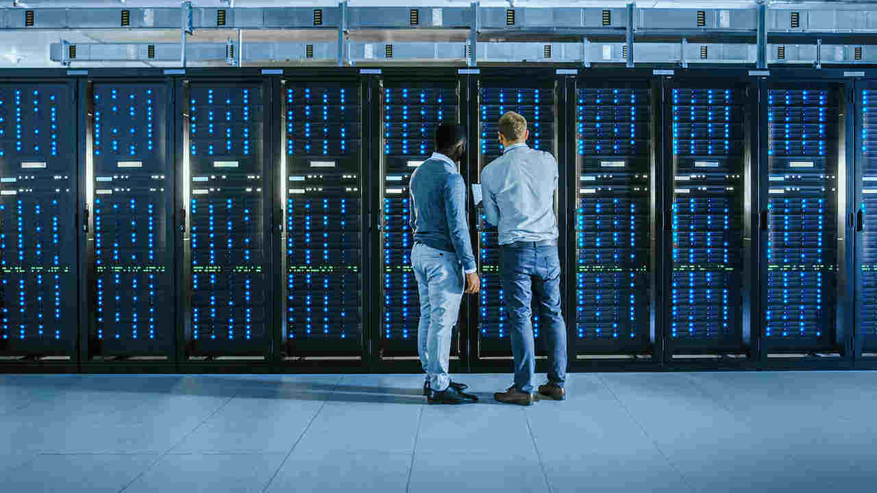 IT technician in glasses with a laptop and male engineer colleague are talking in data center while working next to server racks
