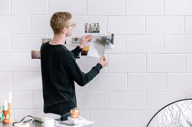 a guy hanging posters of happy customers on a white wall
