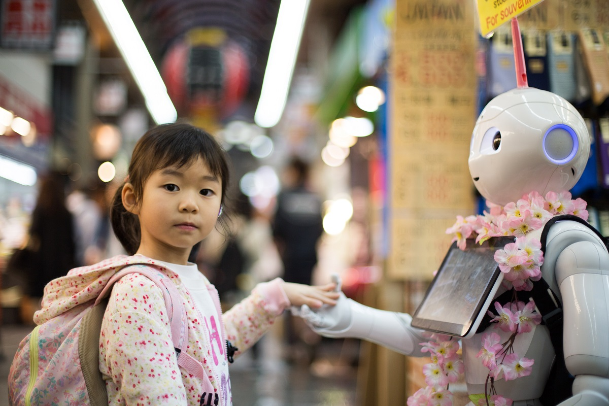 a child shaking hands with a robot