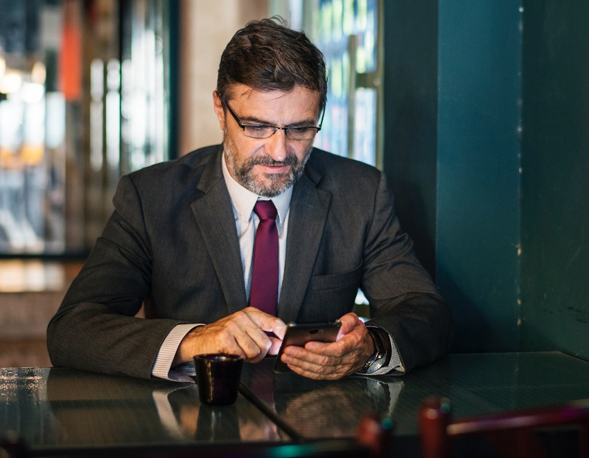 A man in an office with a cell phone