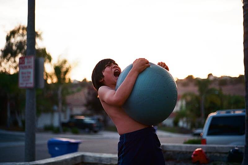 a young boy playing with a gym ball