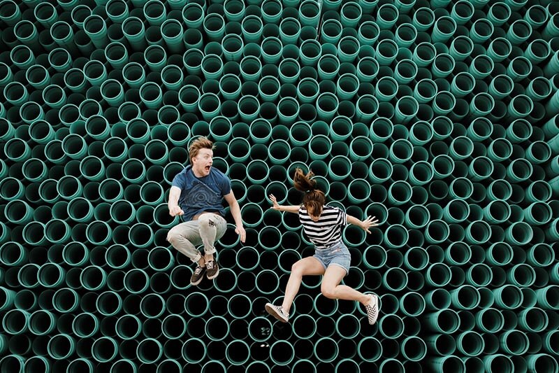 Young girl and a boy jumping on a trampoline