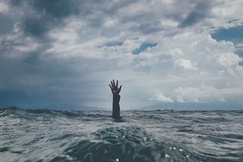 hand in the water of a man drowning into the sea