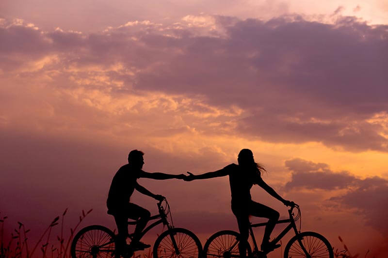 silhouette of a couple cycling together