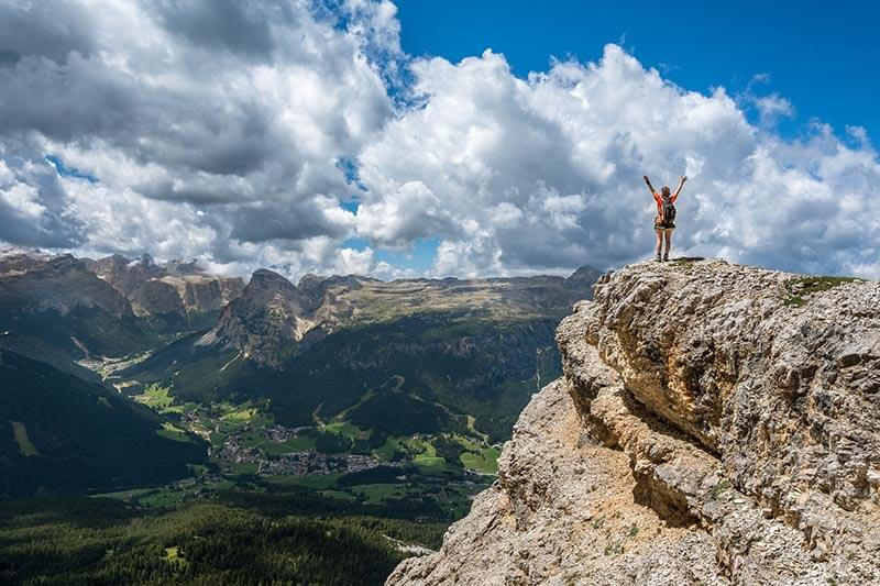 a guy on a cliff celebrating his accomplishment