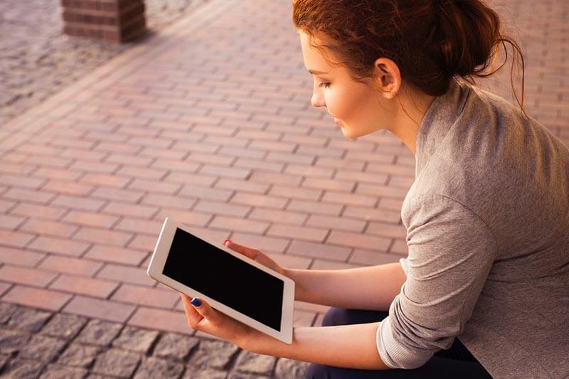 a girl reading a document on her tablet