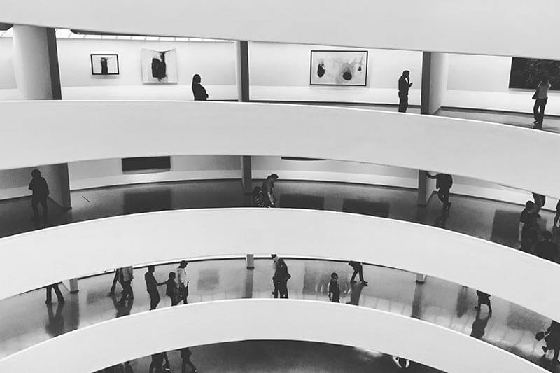 people walking in a white multi-story building at a art gallery