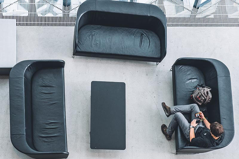 a young guy sitting on a couch inside a building looking at his phone