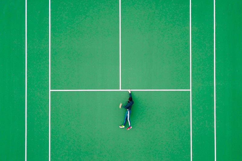 optical illusion of a guy hanging on the markings of a tennis court
