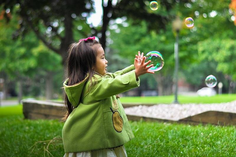 a little girl playing with soap bubbles in a park
