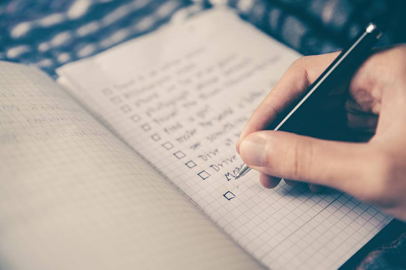 a person writing a checklist on a notebook