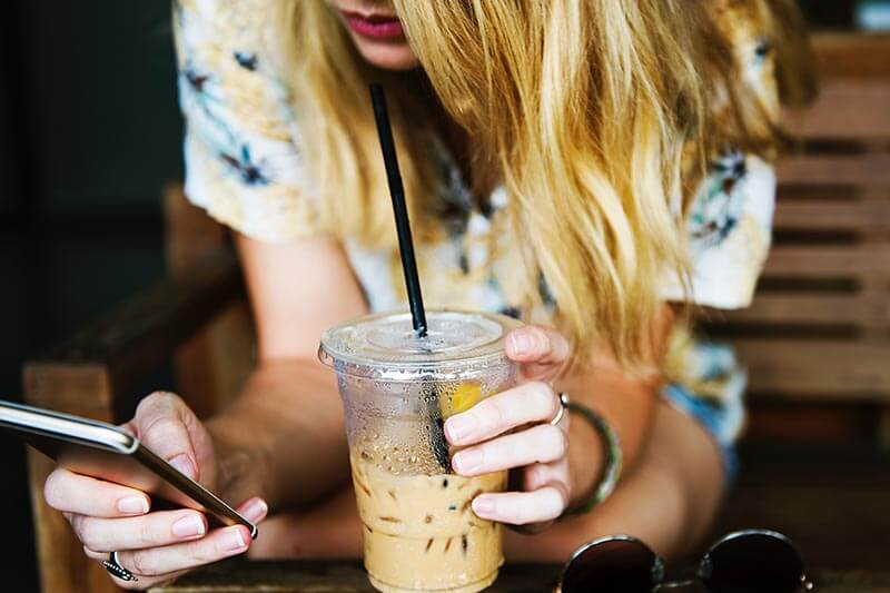 a girl on her cell phone drinks coffee