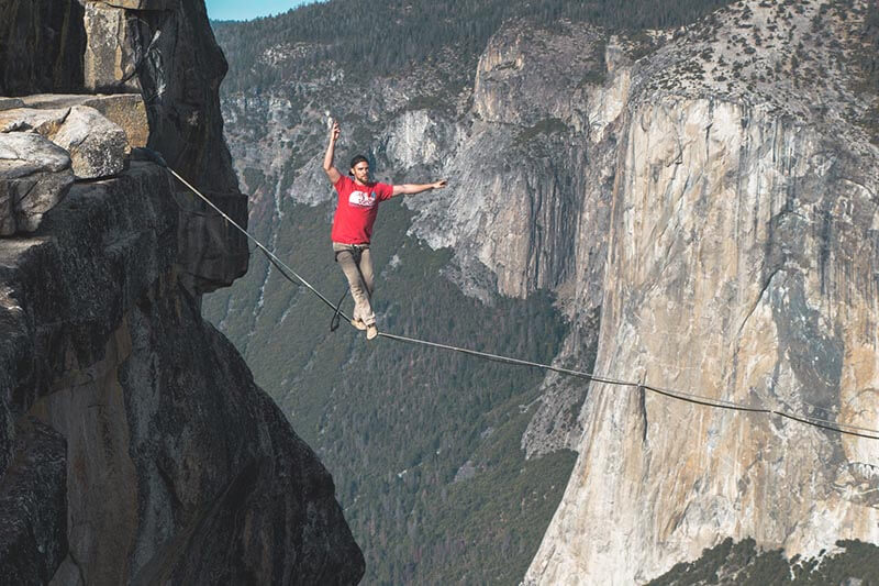 a man walking and balancing on a rope