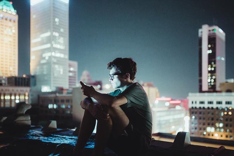 a guy on a terrace at night with his cell phone