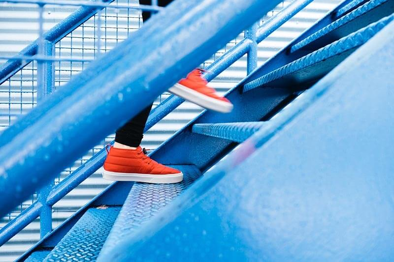 a person with orange shoes climbing blue stairs