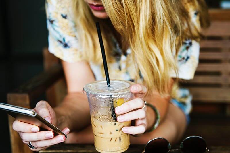 a girl sipping coffee and checking her cell phone