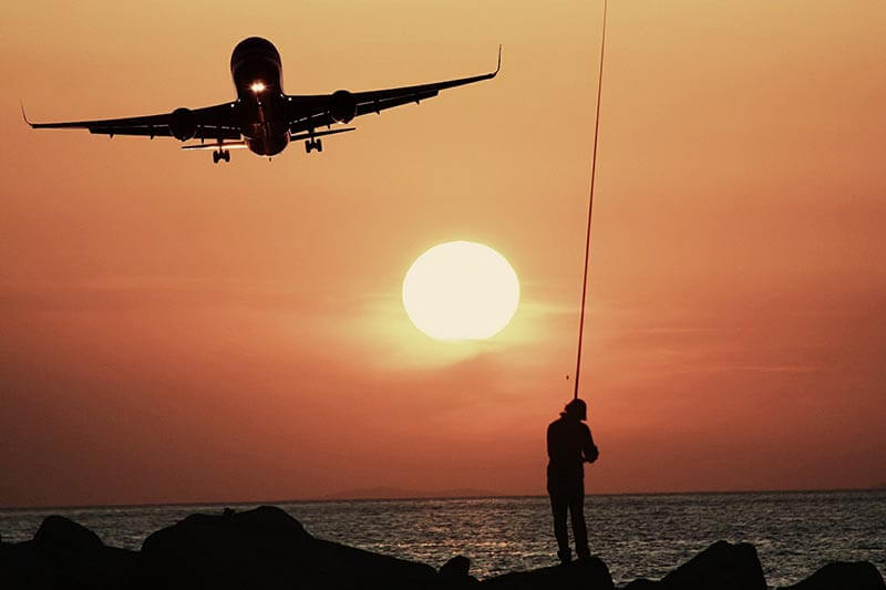 silhouette of a person and a plane on the beach