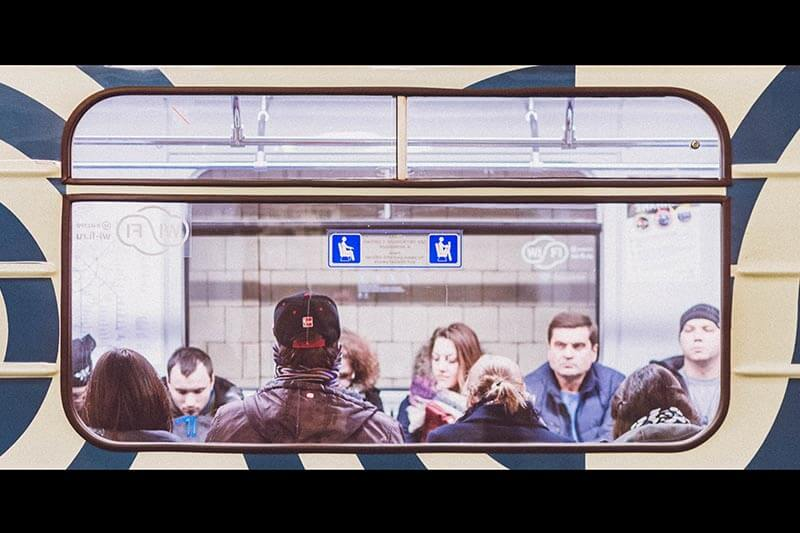 group of people sitting inside a subway train car
