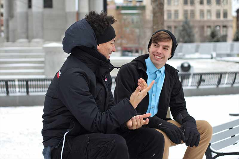 two people sitting on a bench on a snowy day