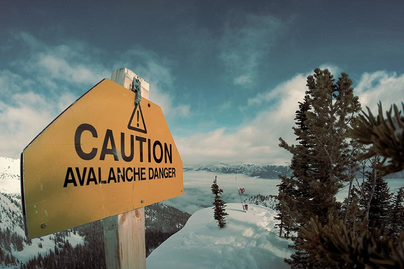 caution sign pointing out the risk of avalanche in the mountains