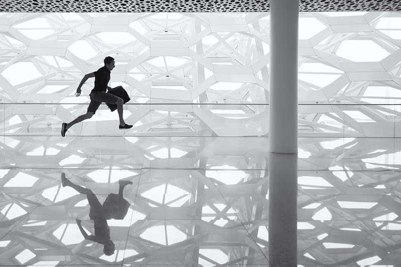 silhouette of a man running with a briefcase through a glass floor