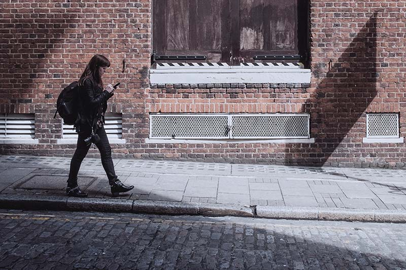 a girl walking on the street with her smartphone