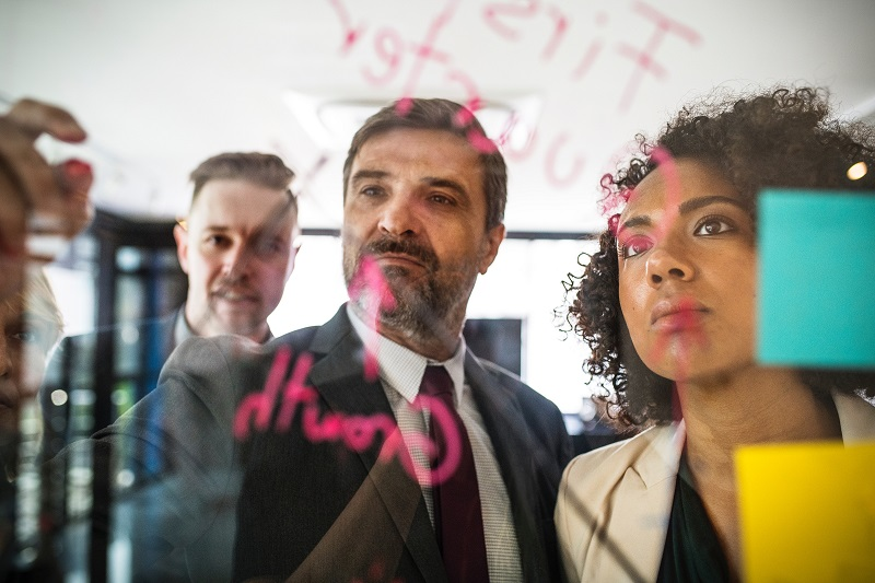 instructional designers in a meeting room writing text on a transparent board