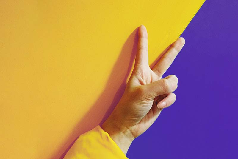 victory sign of fingers on yellow and purple wall