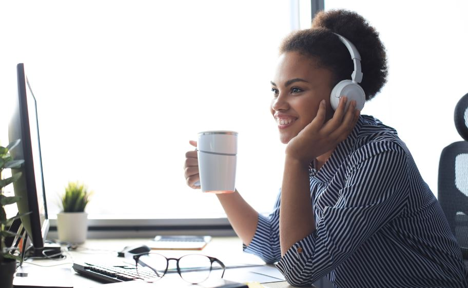 woman sitting in front of computer drinking coffee and attending an online elearning course