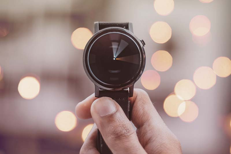 a watch in the hand with blurred background bokeh