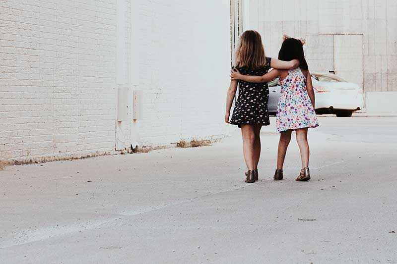 Two young girls walking on the street